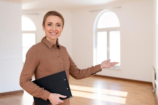 Widok z przodu uśmiechniętej kobiety pośrednika w handlu nieruchomościami, zapraszającej do obejrzenia pustego domu