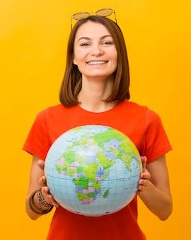 Widok z przodu uśmiechniętej kobiety trzymającej kulę ziemską