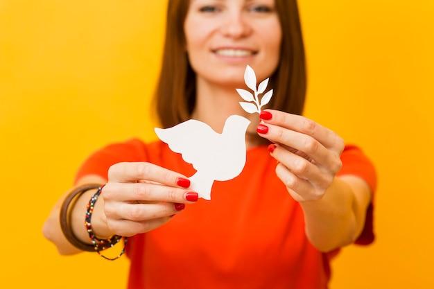 Widok z przodu uśmiechniętej kobiety trzymającej papierową gołębicę