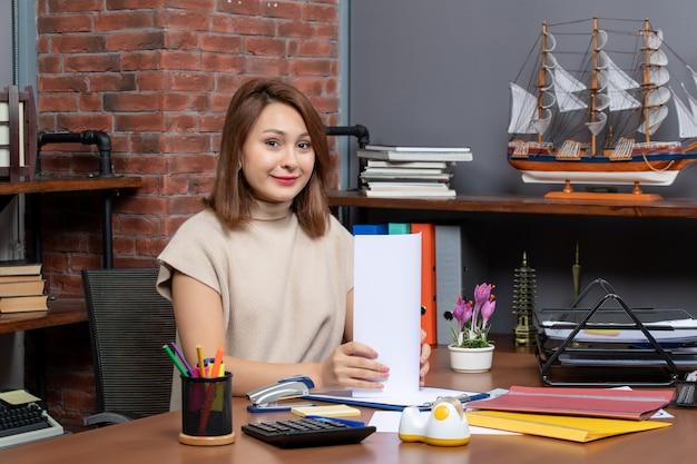 Widok z przodu uśmiechniętej kobiety trzymającej papiery siedzącej przy ścianie