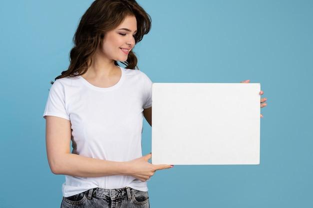 Widok z przodu uśmiechniętej kobiety trzymającej pustą tabliczkę