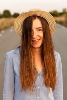 Widok z przodu uśmiechniętej kobiety w kapeluszu stwarzających o zachodzie słońca na drodze