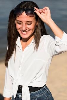 Widok z przodu uśmiechniętej kobiety z okularami przeciwsłonecznymi na plaży