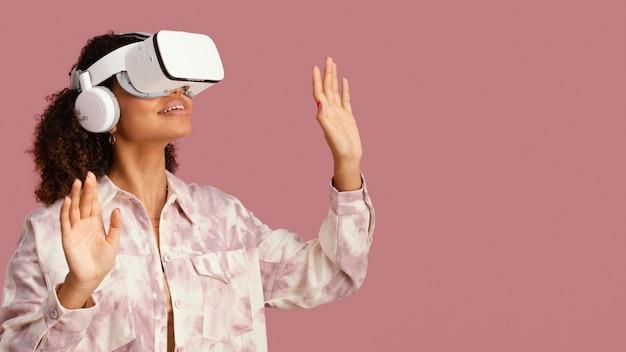 Widok z przodu uśmiechniętej kobiety z zestawem słuchawkowym wirtualnej rzeczywistości i miejsca na kopię
