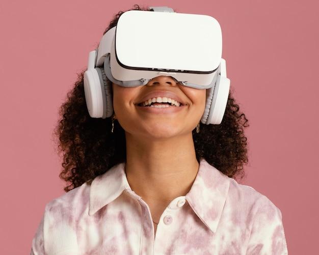Widok z przodu uśmiechniętej kobiety z zestawem słuchawkowym wirtualnej rzeczywistości