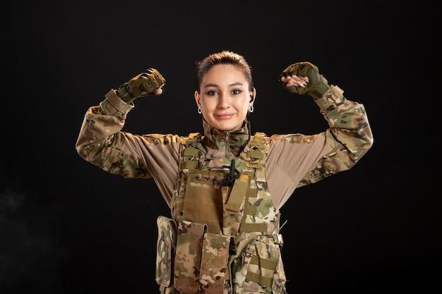 Widok z przodu uśmiechniętej kobiety-żołnierza w czarnej ścianie kamuflażu