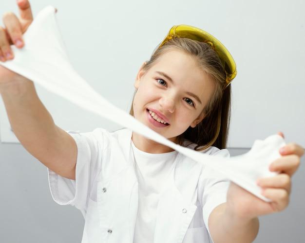 Widok z przodu uśmiechniętej młodej dziewczyny naukowca eksperymentującego ze szlamem