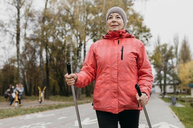 Widok z przodu uśmiechniętej starszej kobiety na zewnątrz z kijami trekkingowymi