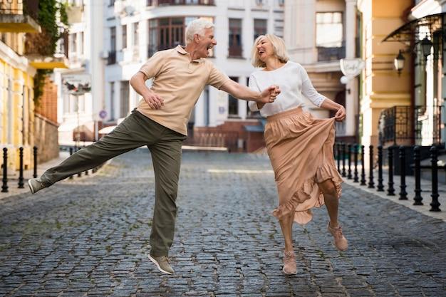 Widok z przodu uśmiechniętej szczęśliwej pary trzymającej się za ręce w mieście