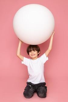 Widok z przodu uśmiechnięty chłopiec dziecko w białej koszulce bawi się białą piłką na różowej przestrzeni