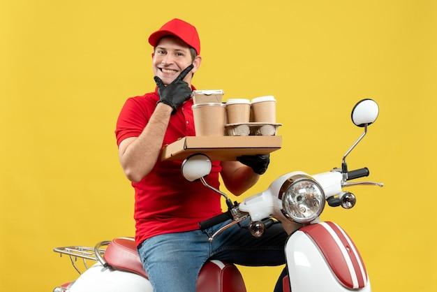 Widok z przodu uśmiechnięty człowiek kurier ubrany w czerwoną bluzkę i rękawiczki kapelusz w masce medycznej dostarczania zamówienia siedzącego na skuterze trzyma zamówienia