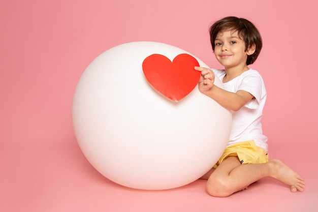 Widok z przodu uśmiechnięty ładny chłopiec w białej koszulce, grający białą piłką na różowym biurku