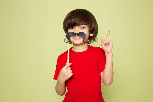 Widok z przodu uśmiechnięty ładny chłopiec w czerwonej koszulce i wąsach na kamiennej przestrzeni