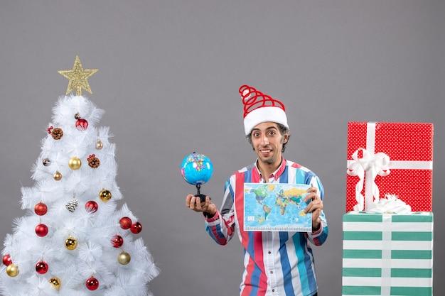 Widok z przodu uśmiechnięty mężczyzna trzyma mapę świata i kulę ziemską