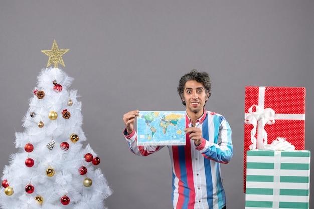 Widok z przodu uśmiechnięty mężczyzna z koszuli w paski, trzymając mapę w pobliżu białego drzewa xmas i przedstawia z miejsca na kopię