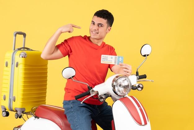 Widok z przodu uśmiechnięty młody człowiek na motorowerze posiadający bilet na żółtym tle