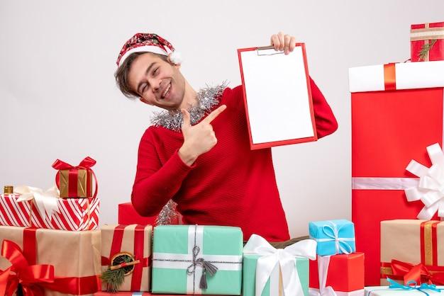 Widok z przodu uśmiechnięty młody człowiek wskazujący schowek palcem siedzący wokół świątecznych prezentów