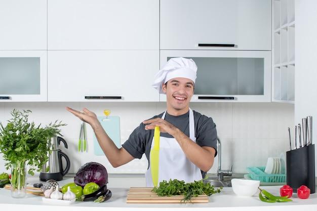 Widok z przodu uśmiechnięty młody kucharz w mundurze, wskazując na lewo