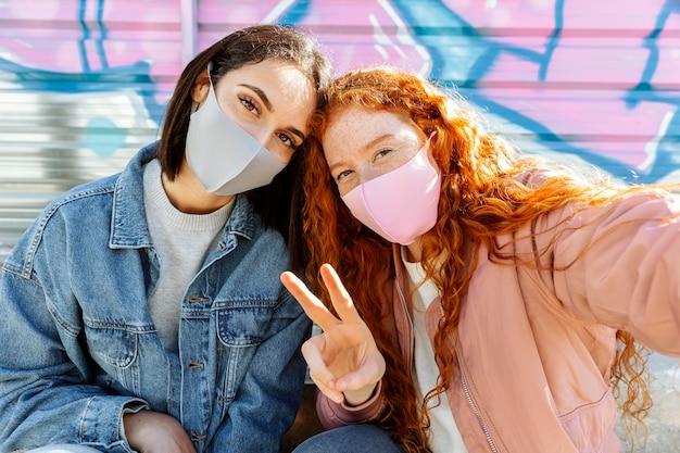 Widok z przodu uśmiechniętych koleżanek z maskami na twarz na zewnątrz, biorąc selfie