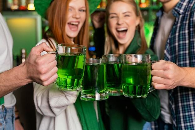Widok z przodu uśmiechniętych ludzi świętujących ul. patrick's day w barze