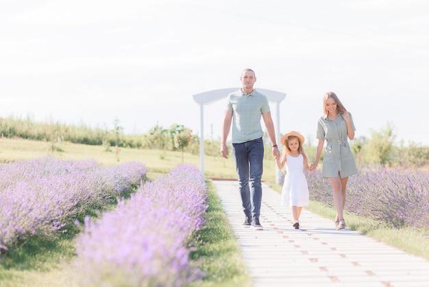 Widok z przodu uśmiechniętych rodziców trzymających się za ręce córki, idących ścieżką w słoneczny dzień