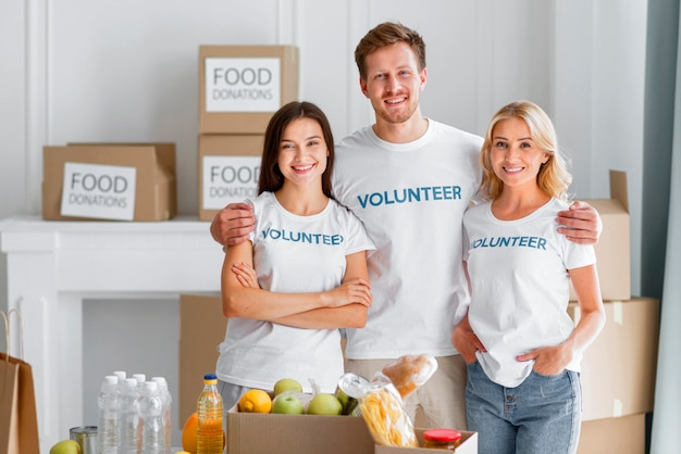 Widok z przodu uśmiechniętych wolontariuszy pozujących z darowiznami żywności