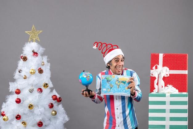 Widok z przodu uszczęśliwiony mężczyzna ze spiralną wiosną santa hat trzyma mapę świata i globus wokół choinki i prezentów