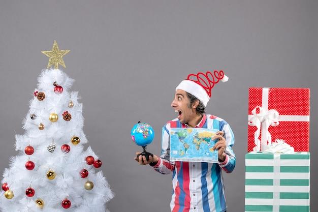 Widok z przodu uszczęśliwiony mężczyzna ze spiralną wiosną santa hat trzyma mapę świata i kulę ziemską