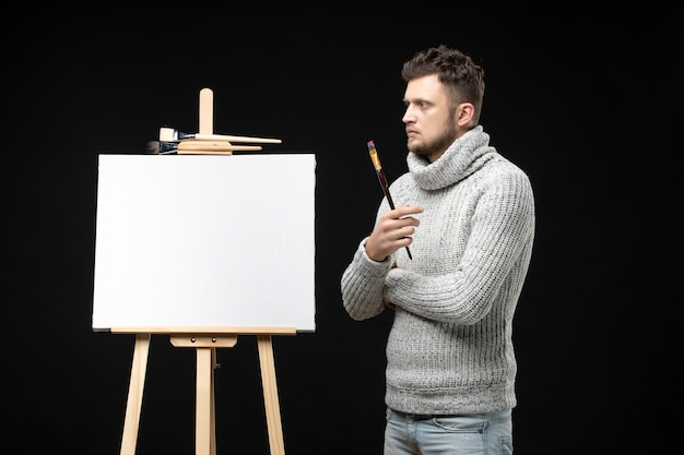 Widok z przodu utalentowanego, rozważnego artysty męskiego skoncentrowanego na czymś na czarno