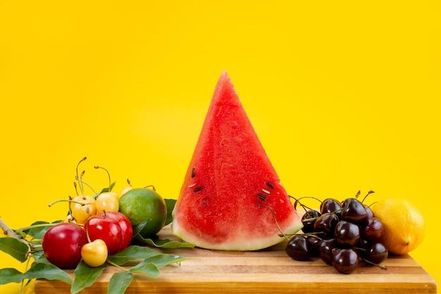 Widok z przodu w plasterkach alogn świeżego arbuza ze świeżymi owocami na żółtym biurku
