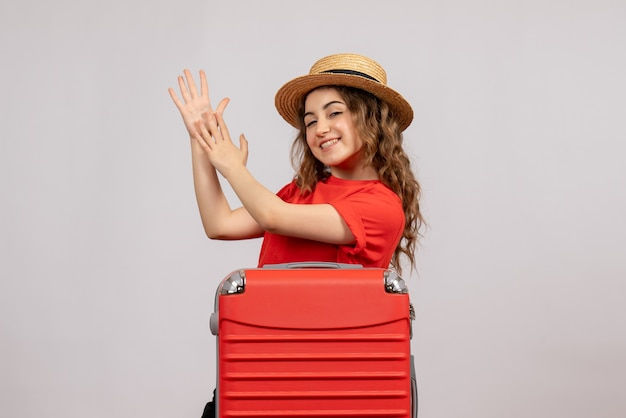 Widok z przodu wakacyjnej dziewczyny z jej walizką, klaszcząc w dłonie, stojąc na białej ścianie