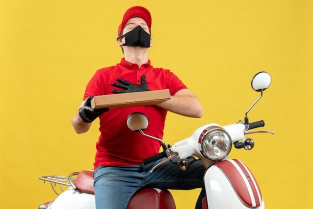 Widok z przodu wdzięcznego kuriera w czerwonej bluzce i rękawiczkach w masce medycznej siedzi na skuterze przedstawiającym porządek