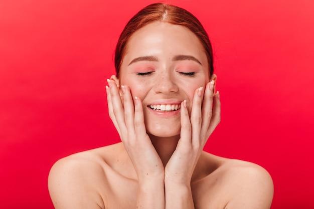 Widok z przodu wesoła dziewczyna imbir dotyka twarzy. studio strzałów podekscytowany nagie kobiety na białym tle na czerwonym tle.