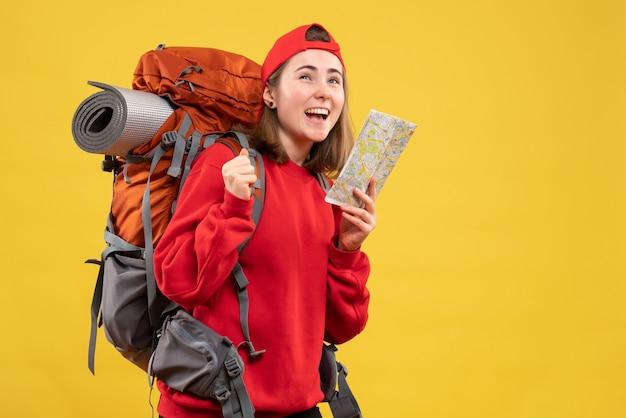 Widok z przodu wesoła kobieta z plecakiem trzymająca mapę podróży