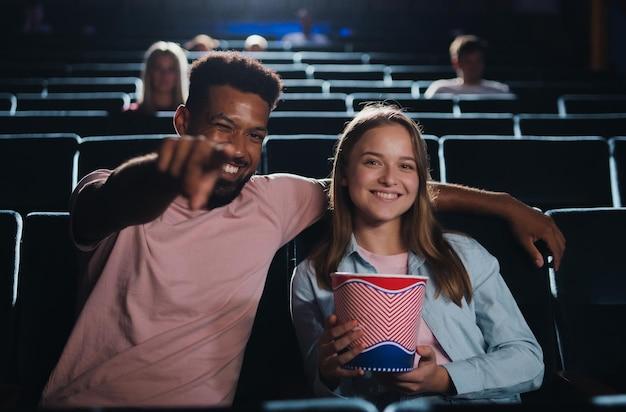 Widok z przodu wesoła młoda para w kinie, wskazując na kamerę.