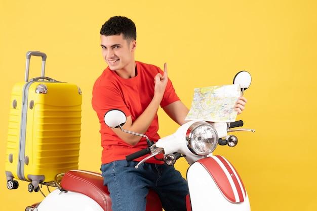 Widok z przodu wesoły młody człowiek na mapie gospodarstwa motoroweru