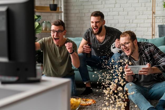 Widok z przodu wesołych przyjaciół płci męskiej, którzy razem oglądają sport w telewizji, jedząc przekąski