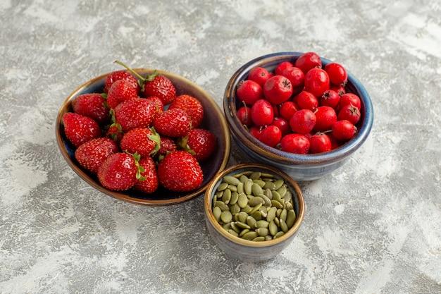 Widok z przodu? wie? e czerwone truskawki na bia? ym stole? wie? e dzikie ro? lin kolor owoce jagodowe