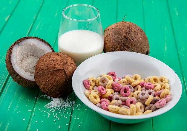 Widok z przodu wielokolorowych zbóż na białej misce z kokosem i szklanką wody na zielonej powierzchni