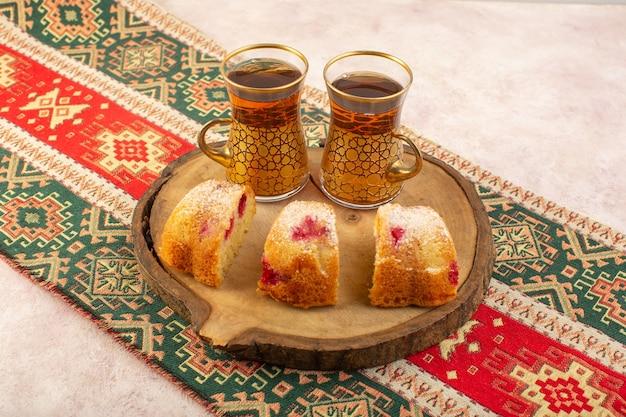 Widok z przodu wiśniowego ciasta w plastry pysznie z herbatą na brązowym drewnianym biurku i różowym biurku