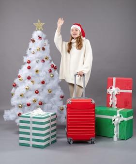 Widok z przodu witająca dziewczyna ubrana w santa hat stojącej w pobliżu prezentów