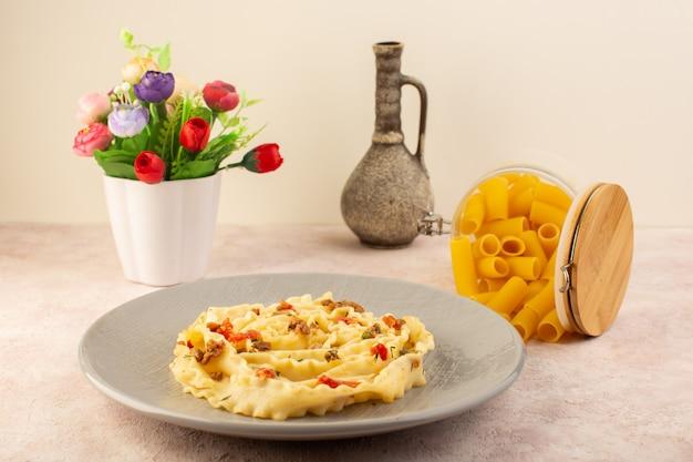 Widok z przodu włoski makaron smaczny posiłek z gotowanymi warzywami i małymi kawałkami mięsa wewnątrz szarej płyty wraz z kwiatem i surowym makaronem na różowo