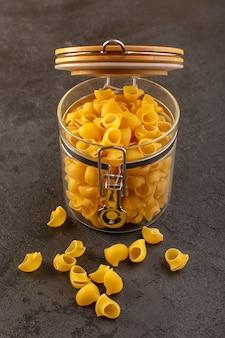 Widok z przodu włoski suchy makaron żółty surowe wewnątrz miski odizolowane w ciemności