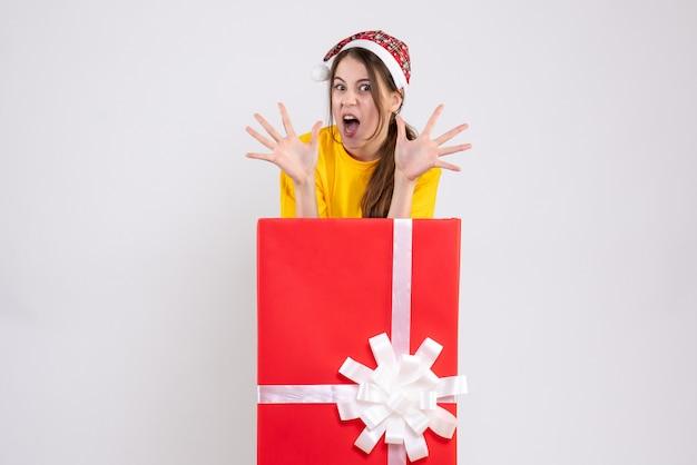 Widok z przodu wściekła dziewczyna z santa hat otwierając ręce stojąc za wielkim prezentem bożonarodzeniowym