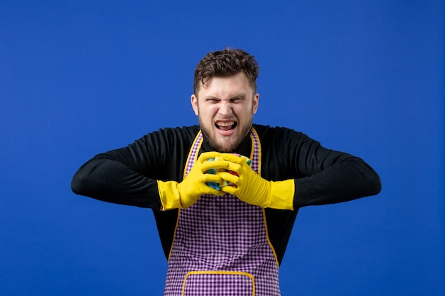 Widok z przodu wściekły mężczyzna gospodyni ściska gąbki na niebieskiej izolowanej przestrzeni