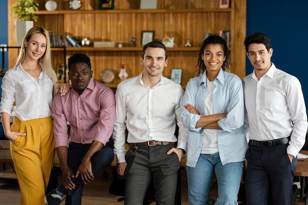 Widok z przodu współpracowników pozujących razem w pracy