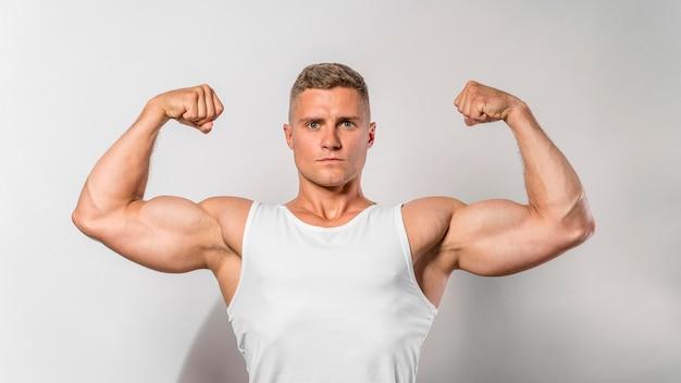 Widok z przodu wysportowanego mężczyzny pokazującego bicepsy
