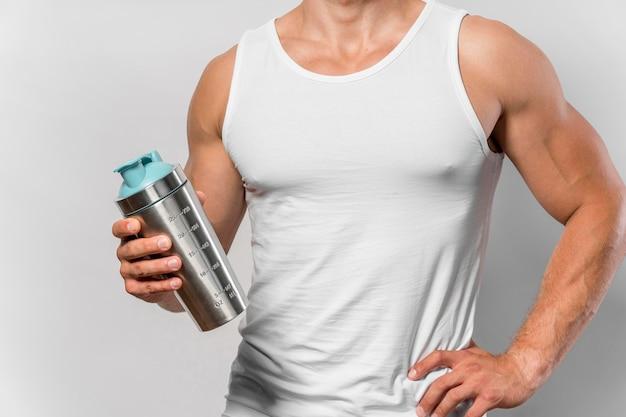 Widok z przodu wysportowanego mężczyzny z podkoszulkiem i butelką wody