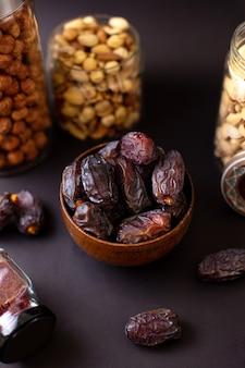 Widok z przodu xurma brązowy smaczny wraz z różnymi orzechami na ciemnej powierzchni
