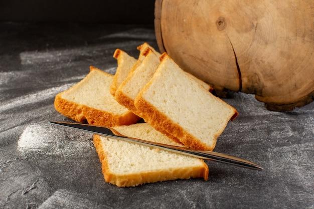Widok z przodu z bliska bochenki białego chleba w plasterkach i smaczne odizolowane srebrnym nożem na szarej powierzchni